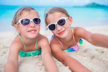 Close up little girls on sandy beach. Happy kids lying on warm white sand