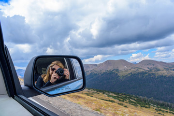 woman taking photo of rocky mountains out car window reflected in rear view mirror
