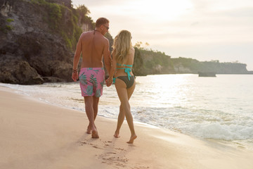 Romantic couple walking on the beach in evening