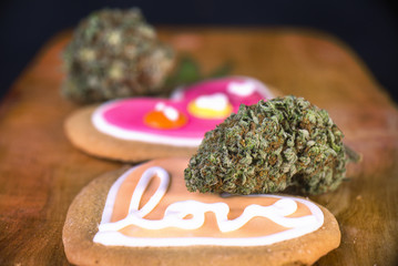 Dried cannabis nug with baked cookies on a wood tray