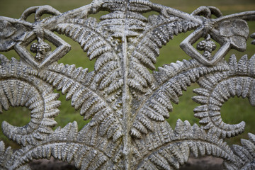 Isolated View of Decorative Fern Pattern Wrought iron Work Against Out of Focus Green Grass in Background