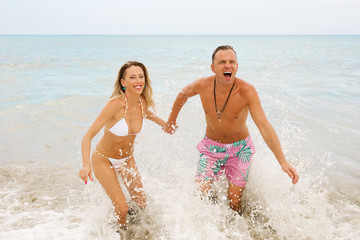 Couple laughing in ocean waves