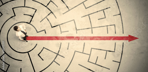 Wall mural Business person standing in the middle of a circular maze