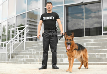 Security guard with dog near building