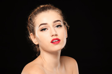 Portrait of young woman with beautiful eyebrows on dark background
