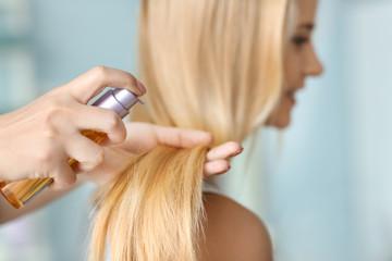 Stylist applying oil onto woman's hair, indoors