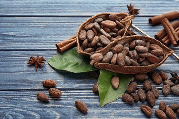 Halves of cocoa pod with beans on wooden table