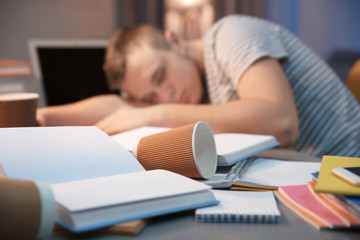 Coffee cup and sleeping student on background, closeup