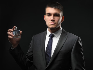 Handsome man in formal suit and with bottle of perfume on dark background