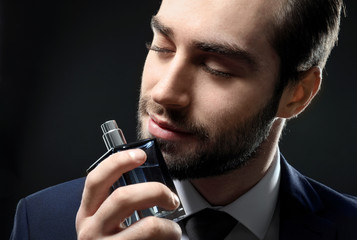 Handsome man in formal suit and with bottle of perfume on dark background, closeup