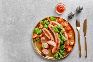Plate with delicious grilled sausages, tomato and basil on grey background