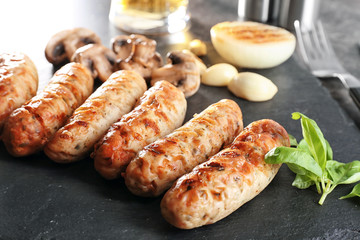 Slate plate with delicious grilled sausages, closeup