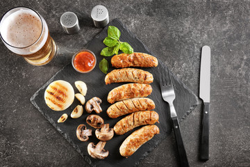 Slate plate with delicious grilled sausages and vegetables on dark background