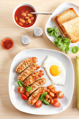 Plate with delicious grilled sausages and fried egg on wooden background