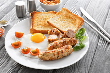 Plate with delicious grilled sausages, toasts and fried egg on wooden table