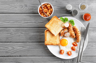 Plate with delicious grilled sausages, toasts and fried egg on wooden background