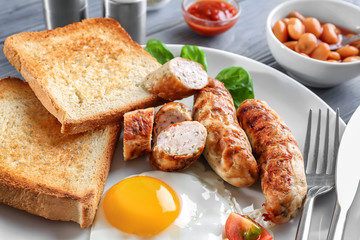Plate with delicious grilled sausages, toasts and fried egg, closeup