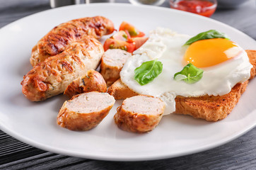 Plate with delicious grilled sausages and fried egg, closeup