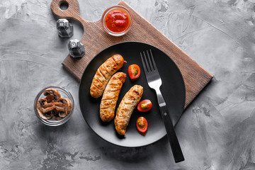 Plate with delicious grilled sausages on wooden board