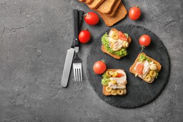 Slate plate with tasty chicken bruschettas on table
