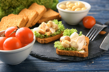 Slate plate with tasty chicken bruschettas and ingredients, closeup