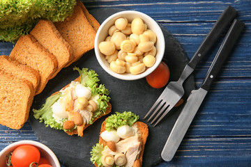 Slate plate with tasty chicken bruschettas and ingredients on table