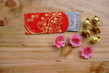 Chinese new year festival decorations ingots, red packet (ang pow) and Malaysian Ringgit banknote and sakura flower on wooden background with copy space