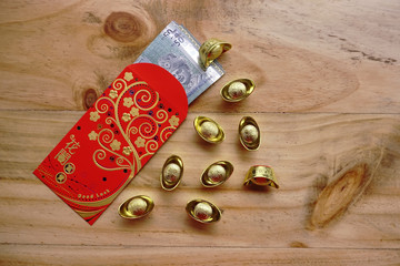 Chinese new year festival decorations ingots, red packet (ang pow) and Malaysian Ringgit banknote on wooden background with copy space