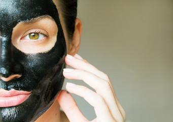 a girl in a black coal mask