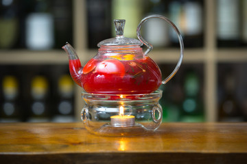 Red tea in a teapot on a stand with a candle on wooden bar counter. On background rack with bottles.