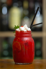 Red smoothies with marshmallow on wooden bar counter. On background rack with bottles.