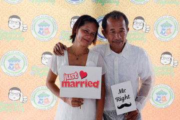 A couple poses at a wedding photo booth before the start of a free mass wedding ahead of Valentine's Day celebration at Subic, Zambales