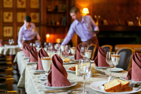 Waiters prepare a table for breakfast. Background. The foreground of napkins, dishes, toast, glasses. Calm atmosphere
