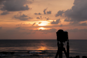A silhouette of a DSLR Camera shooting the dramatic sunset by the beach.