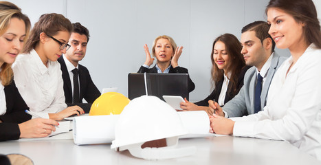 Mature blonde woman leads meeting of architects