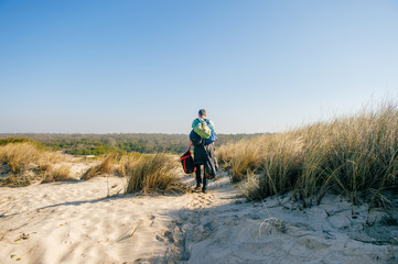 Homeless hermit carrying many bags with belongings in sandy dunes beyond sea in sunny day. Man from behind travelling alone. Unknown male with backpacks and heavy buggage in hands hiking outdoor.