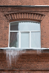 Window sill covered with big icicles, horizontal/ ice stalactite hanging from window sill/ Poor thermal insulation of the roof leads to the formation of icicles/ Many little icicles