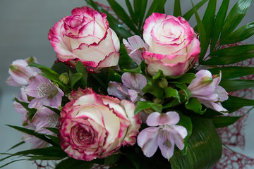 A wonderful bouquet of white roses with red flowers and spring flowers