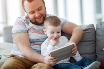 Image of daddy with his son with tablet sitting on gray sofa
