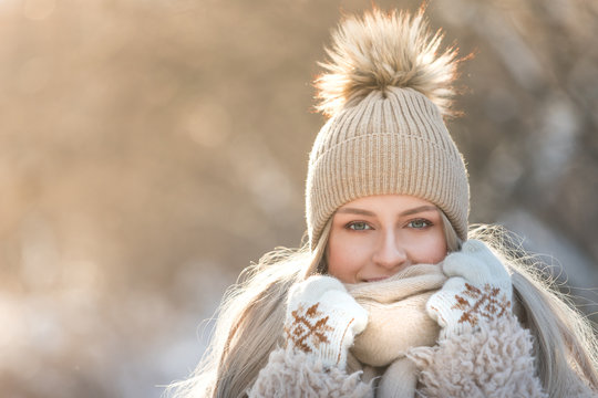 Close portrait of young caucasian woman with long hair in beige hat with fur pompon, scarf, coat, white gloves at sunny winter day, / Female wrap in and holding scarf, looking at camera, copy space