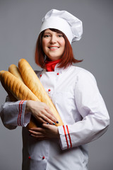 Image of woman cook in white robe and cap with loaves