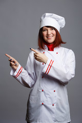 Photo of smiling chef girl in white robe pointing fingers at empty space