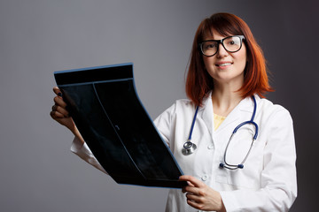 Picture of brunette doctor in glasses and white coat with X-ray