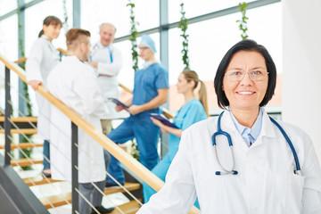 Ältere Frau als Chefin vor ihrem Ärzteteam