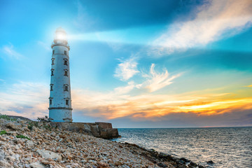 Canvas Prints Port Lighthouse searchlight beam through sea air at night. Seascape at sunset