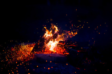 Burning wood at night. Campfire at touristic camp at nature in mountains. Flame amd fire sparks on dark abstract background. Cooking barbecue outdoor. Hellish fire element. Fuel, power and energy.