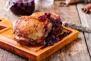 Roast chicken legs on cutting board with cranberry sauce