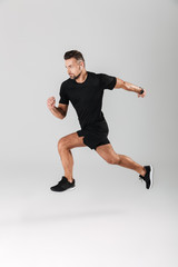 Full length portrait of a strong mature sportsman jumping