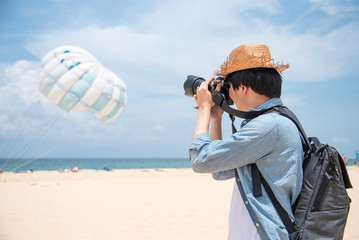 Young Asian man photographer in jean shirt take photo of parasailing on the beach of Phuket, Thailand