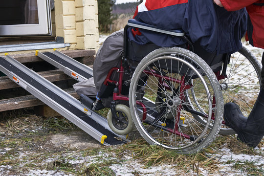 Lifting an invalid in a wheelchair into a country house using metallic guides